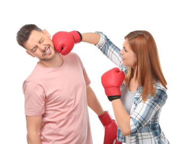 Angry couple in boxing gloves fighting on white background
