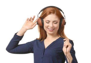 Portrait of beautiful smiling woman listening to music on white background