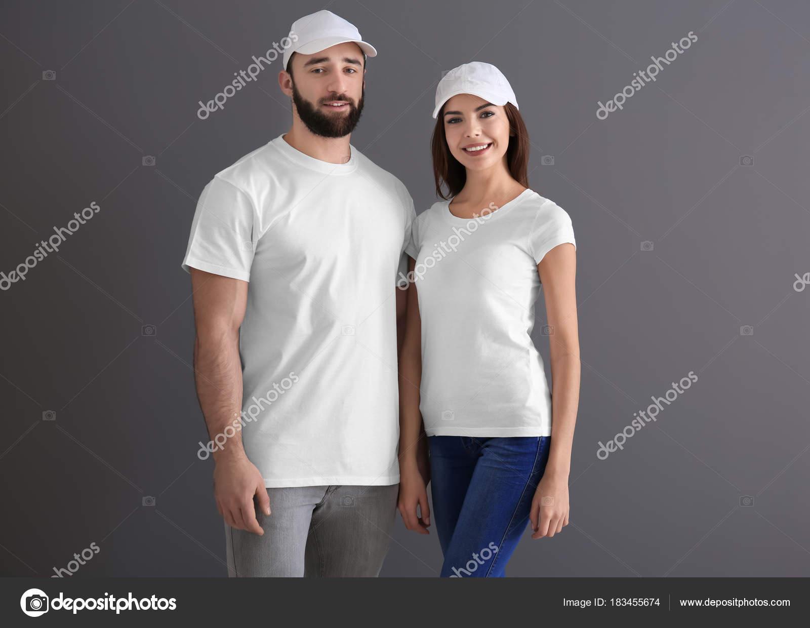 b8c2c4c8f6 Młody mężczyzna i kobieta w stylowe białe koszulki na szarym tle. Makieta  do projekt– obraz stockowy