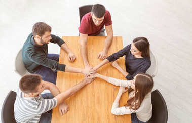 People holding hands together at table. Unity concept