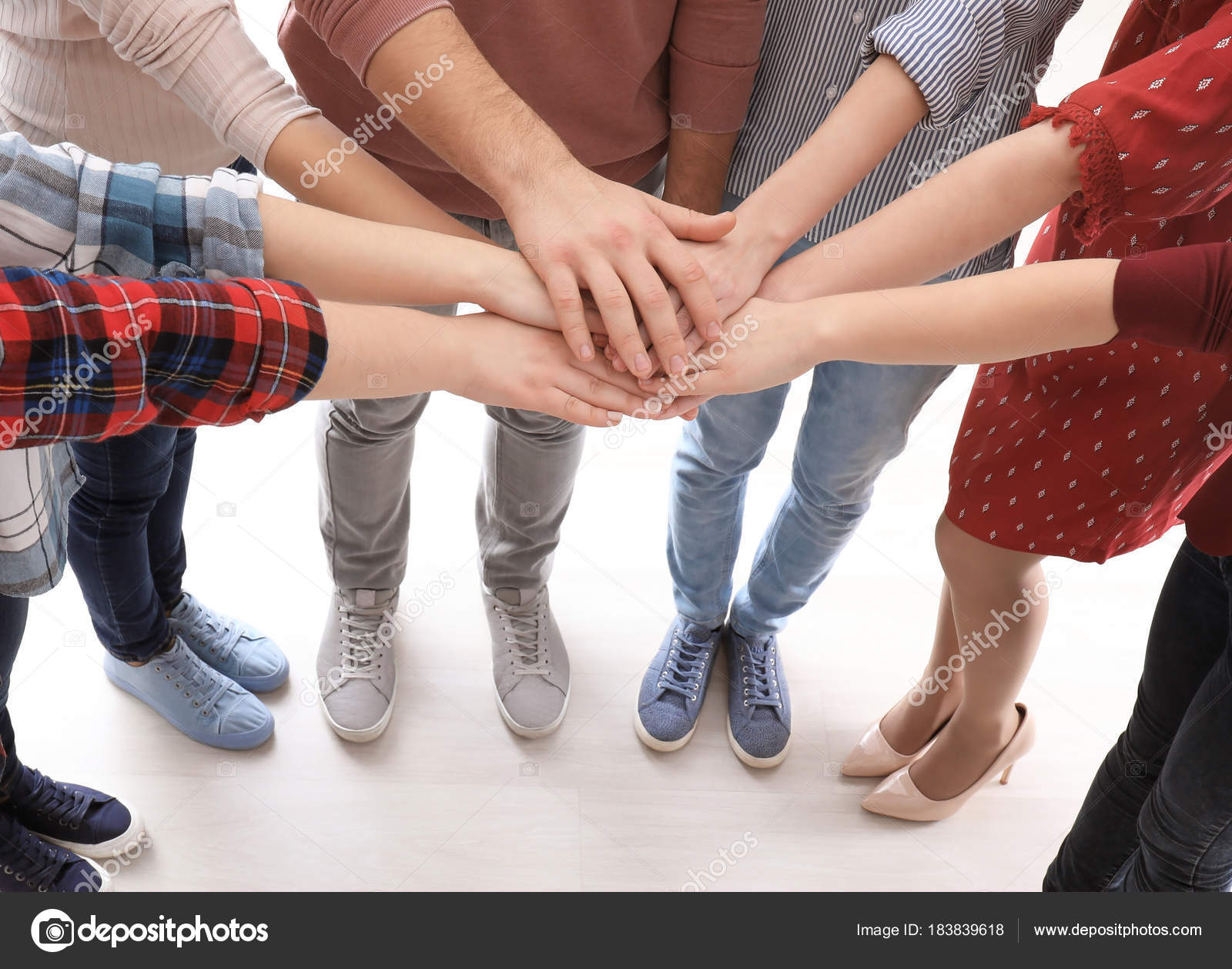 Young people putting hands together as symbol of unity ...