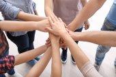 Junge Menschen, die Hände zusammenlegen als Symbol der Einheit
