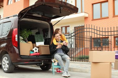 Young couple having break near their car on moving day