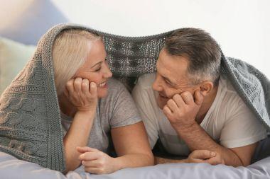 Senior couple under plaid on bed together
