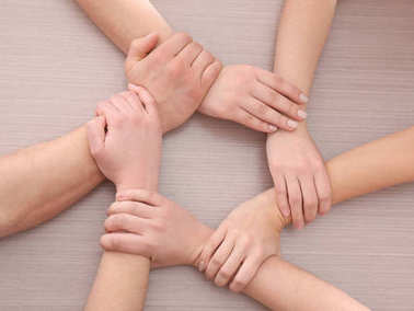 Group of people making circle with their hands on wooden background. Unity concept