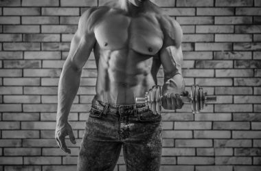 Muscular young bodybuilder with dumbbell on brick wall background, black and white effect