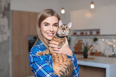 Beautiful young woman with cute cat in kitchen