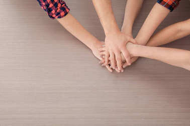 Group of people putting hands together on wooden background. Unity concept