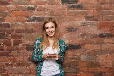 Beautiful young woman with mobile phone near brick wall