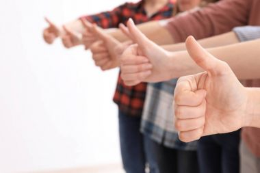 Group of people showing thumb-up gesture on light background. Unity concept