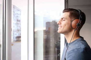 Relaxed young man listening to music near window at home