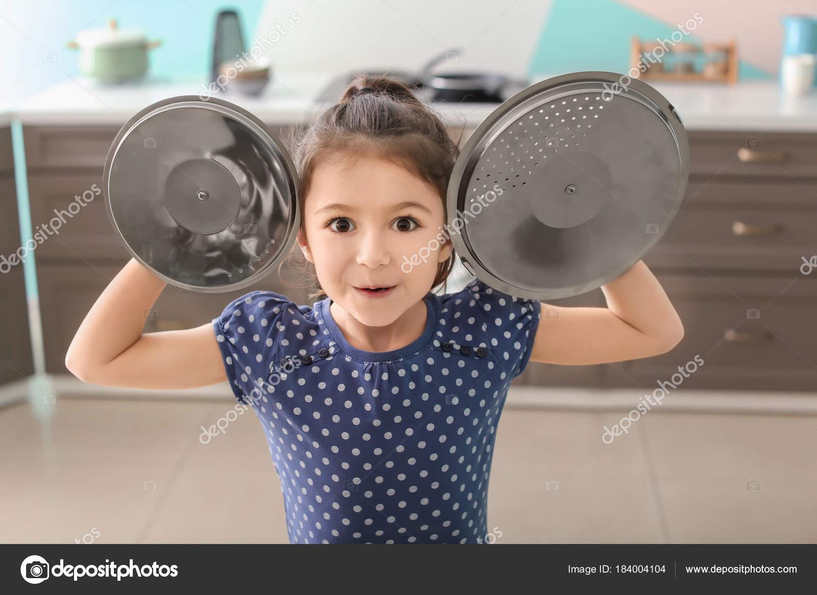 Niedliche kleine Mädchen spielen mit Topf Kappen als Becken in Küche ...