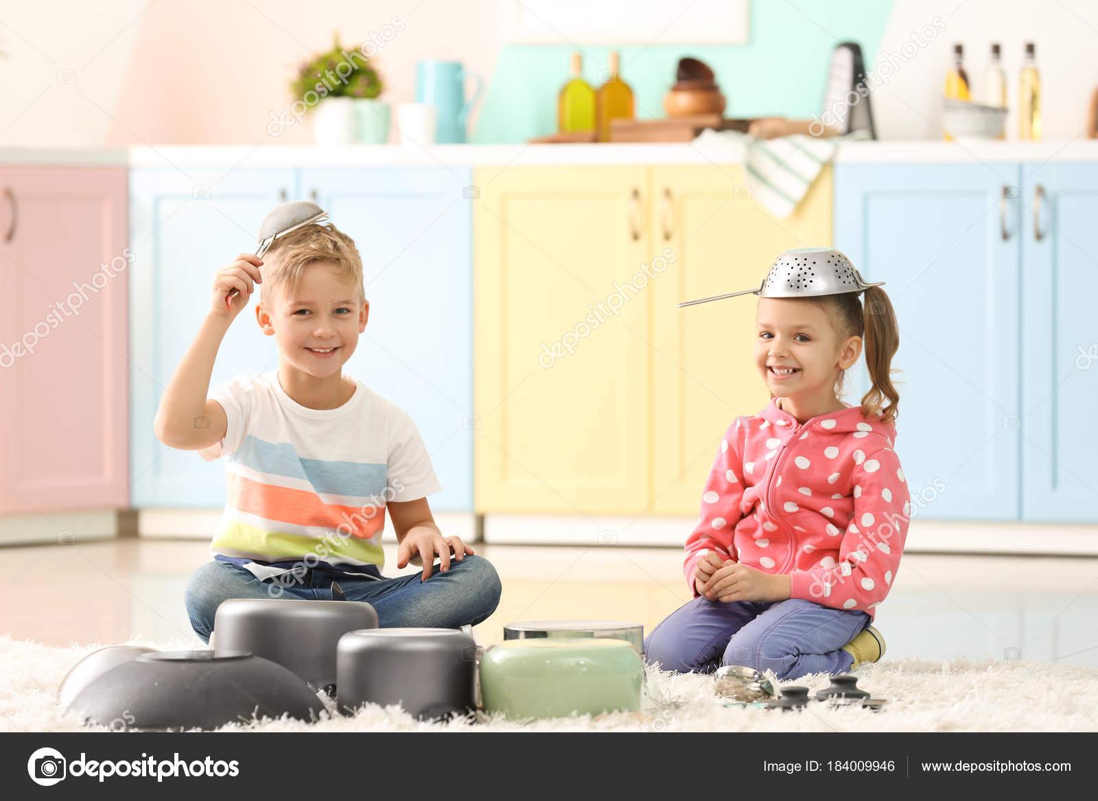 Lindos niños pequeños jugando con utensilios de cocina en casa ...