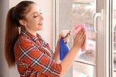 Mladá žena čištění okno uvnitř