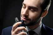 Handsome man with bottle of perfume