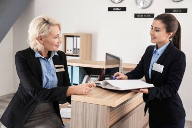 Female receptionist teaching trainee in hotel