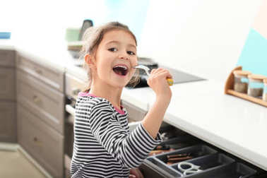 Cute little girl signing song into spoon in kitchen
