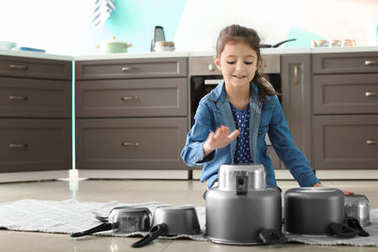 Cute little girl playing with kitchenware as drums in kitchen