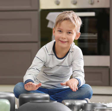 Cute little musician playing drums on kitchenware at home