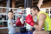 Photo Little boy training with coach in boxing ring