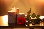Fotografie Brennende Kerzen und schöne Rose auf Tisch