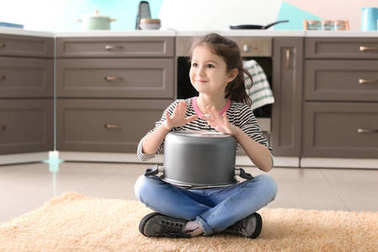 Cute little girl playing with saucepan as drum indoors