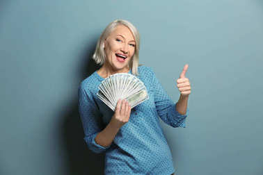 Happy mature woman with money showing thumb-up gesture on color background