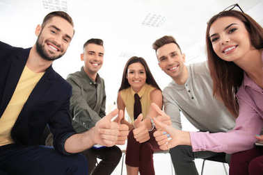Group of specialists showing thumb-up gesture in office