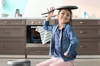 Cute little girl having fun in kitchen
