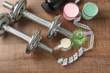 Composition with different protein powders, shakes and dumbbells on wooden background