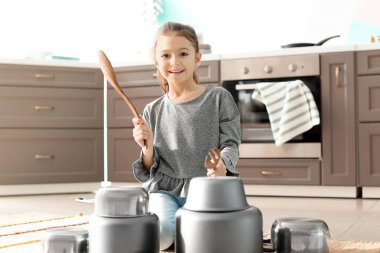 Cute little girl playing with kitchenware as drums indoors