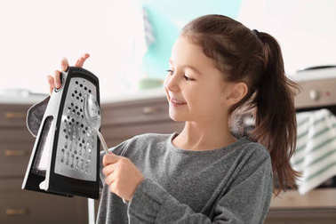 Cute little girl playing music with grater and spoon in kitchen