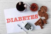 Složení s slovo Diabetes, sladkosti a digitální glukometr na dřevěné pozadí