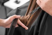 Profesionální stylistka řezání vlasy v salonu, closeup