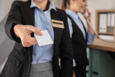 Female receptionist with card in hotel