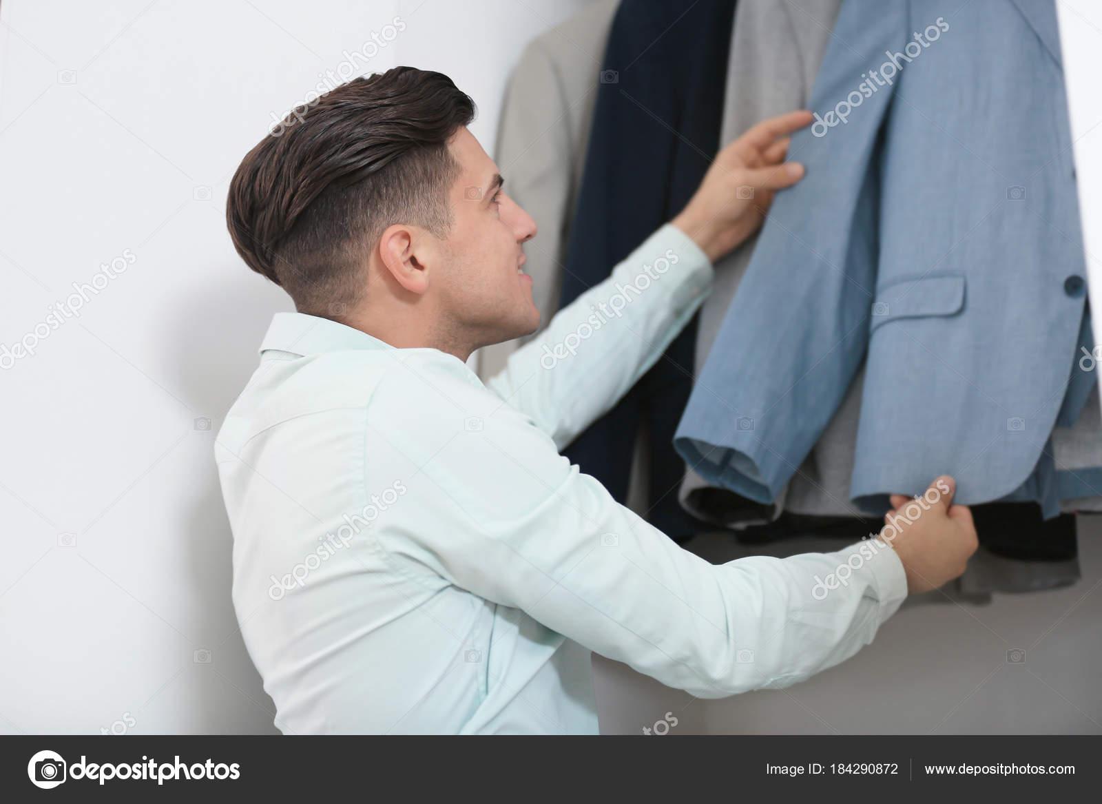 Man Plukken Jas Uit De Kast Stockfoto Belchonock 184290872