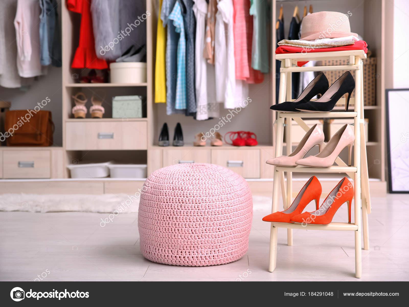 Silla rosa otomana y el soporte con los zapatos en el vestidor ...