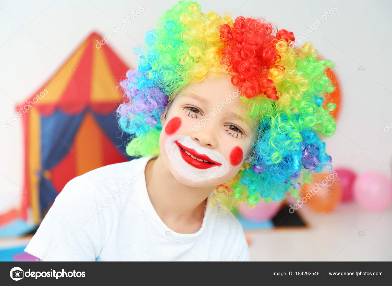 Cute little boy with clown makeup in rainbow wig indoors. April fool's day celebration– stock image