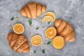 Ízletes croissant pohár narancslé és gyümölcs az asztalon