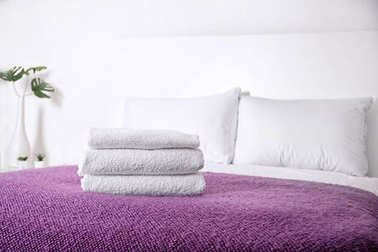 Comfortable bed with folded towels in room interior