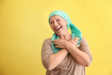 Mature woman with cancer in headscarf on color background