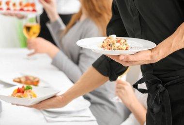 Waiter serving tasty dishes