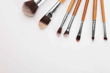 Different brushes of professional makeup artist on white background stock vector