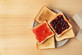 Photo Delicious toasts with sweet jams on table