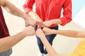 Fotografie Junge Menschen setzen Hände zusammen drinnen. Einheit-Konzept