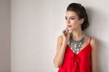 Beautiful young woman with elegant jewelry on light background