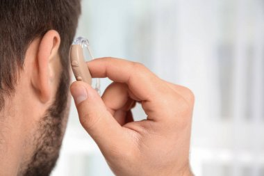 Young man putting hearing aid in ear indoors