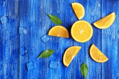 Juicy ripe oranges and ice cubes on wooden background