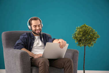 Handsome man with laptop listening to music while sitting in comfortable armchair at home