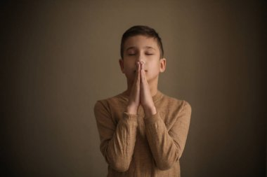 Little boy praying on dark background